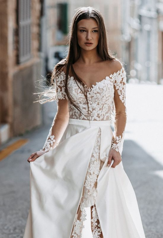 Hedda by Abella Bride long sleeve wedding dress with lace details and slit in skirt at Love it at Stella's Bridal in Westminster, MD