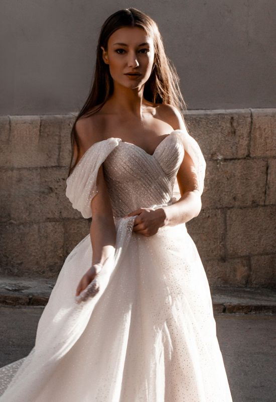 Gita Marie by Abella Bride off the shoulder glitter ballgown with exposed corset and ruched bodice at Love it at Stella's Bridal Shop in Westminster, Maryland